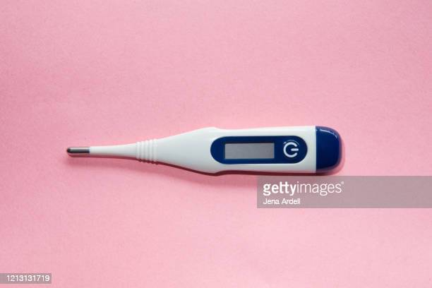digital thermometer on pink background: conceptual image for fertility, women's health and wellness - digital thermometer ストックフォトと画像