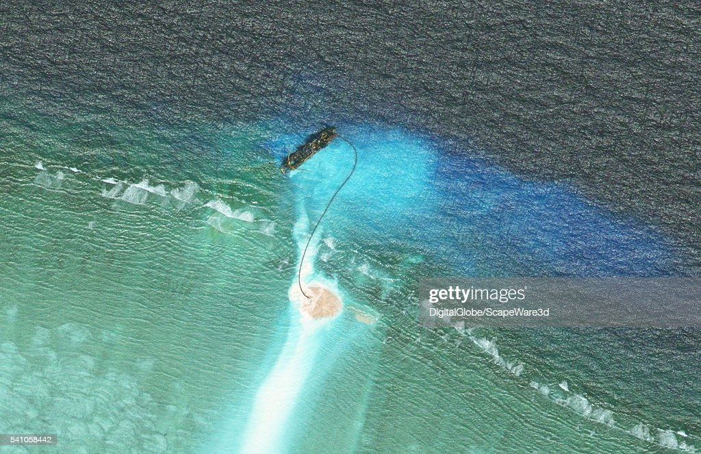 DigitalGlobe closeup imagery of one of the Cuarteron Reef. (This is image 1 of 3 of the before-after sequence.) The Cuarteron Reef is located at the east end of the London Reefs in the Spratly Islands of the South China Sea. Photo DigitalGlobe via Getty Images.