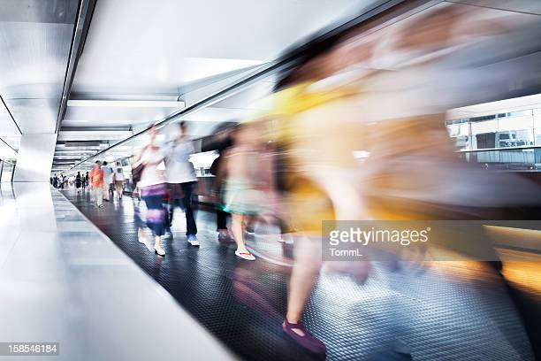 Digitally altered motion view of people at subway station.