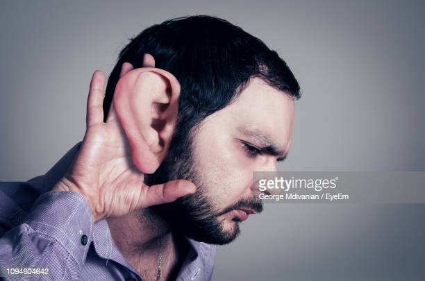 Digitally Enhanced Image Of Man With Large Ear Listening Against Gray Background