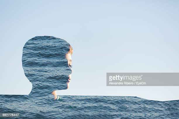 Digitally Generated Image Of Boy And Sea Against Clear Sky