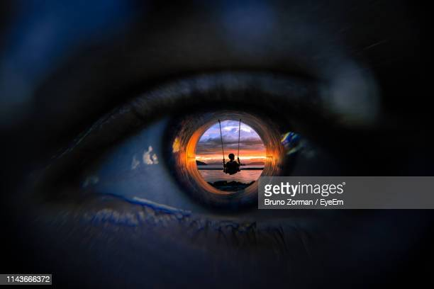 digitally generated image of boy swinging at beach reflecting on man eyeball - eyesight stock photos and pictures