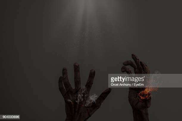 Digitally Generated Image Of Hands Burning Against Gray Background