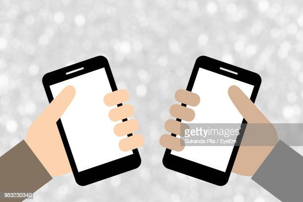 Digitally Generated Image Of Hands Holding Smart Phones
