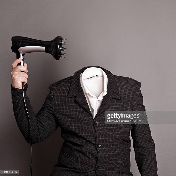 digitally generated image of headless man holding hair dryer against gray background - headless man stock pictures, royalty-free photos & images