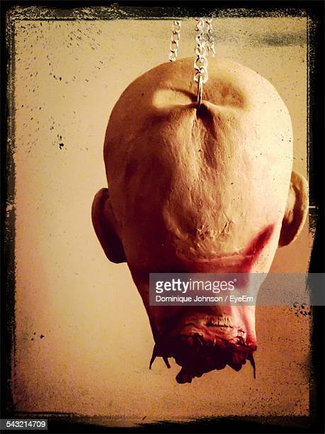 Digitally Generated Image Of Human Head Hanging On Chain Against Wall