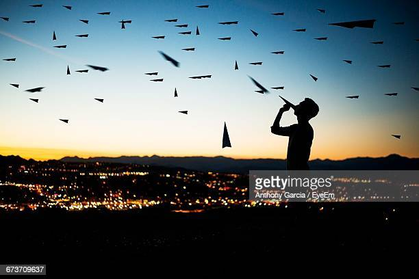 digitally generated image of man standing amidst flying paper airplane during sunset - santa clarita stock pictures, royalty-free photos & images