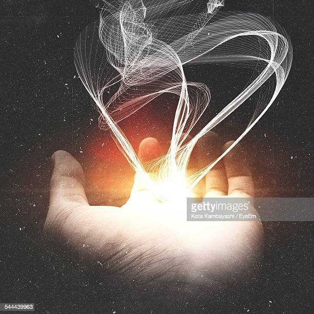 Digitally Generated Image Of Smoke Emitting From Glowing Hand Against Black Background