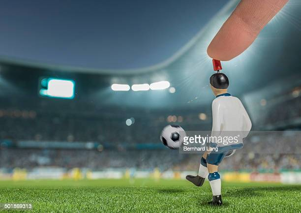 Digitally generated image of soccer player kicking ball in floodlit stadium