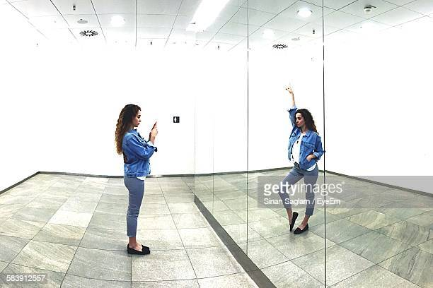Digitally Generated Image Of Woman Photographing Herself In Mirror At Illuminated Room