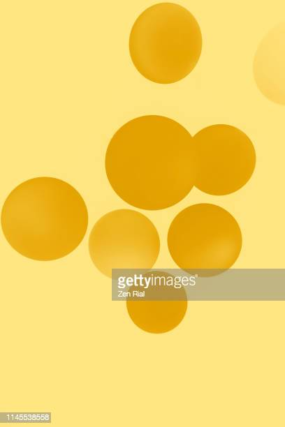 digitally manipulated image of circular drop lights against yellow background - toned image stock pictures, royalty-free photos & images