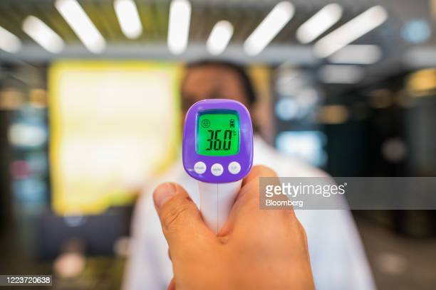Digits on a thermometer read 36 degrees Celsius as a visitor has their temperature checked in the reception area of offices in London, U.K., on...