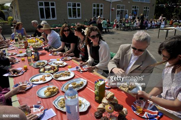 Dignitaries and invited guests on the toptable tuck into the party food at the Bucklebury Church of England Primary School Royal wedding party in the...