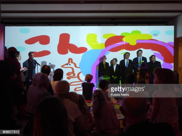 Dignitaries and speakers gather for a photo in front of a projected art work created during Join the Dots at the Sydney Opera House on Jan 16 2018...