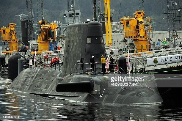 Dignitaries board the submarine after a ceremony to officially make 'Artful' a commissioned warship of the Royal Navy at Faslane Naval Base Rhu...