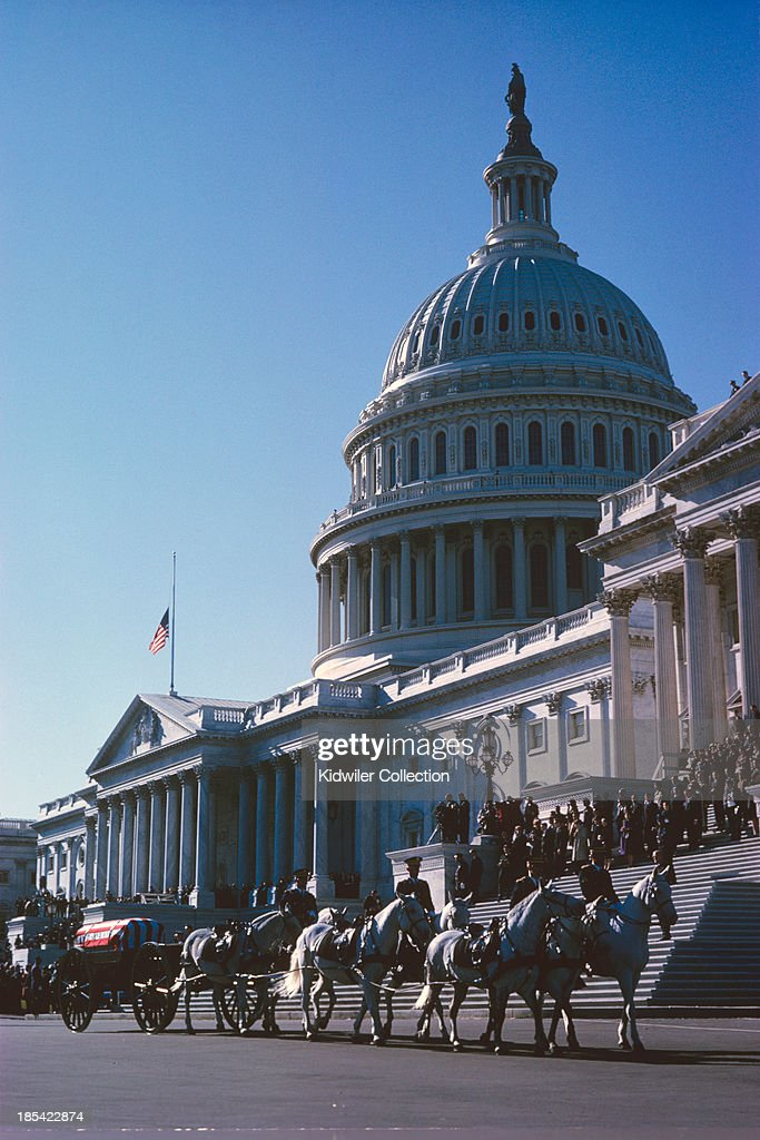 Dignitaries gather on the East steps of the United States Capitol Building as the limbers and caissons carrying the casket proceed to the White House during the funeral for President of the United States John F. Kennedy on November 25, 1963 in Washington, DC. The caisson was followed by one honor guard carrying the flag of the President of the United States and another escorting the riderless horse, Black Jack, in the funeral procession. Kidwiler Collection/Diamond Images