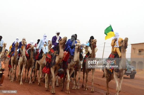 Dignitaries in traditional attires ride camels to the stadium in Gao on July 18 2018 as the incumbent Malian President Ibrahim Boubacar Keita is...