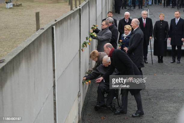 Dignitaries, including German Chancellor Angela Merkel and politician Wolfgang Schaeuble, stick flowers into slats of a still-standing portion of the...