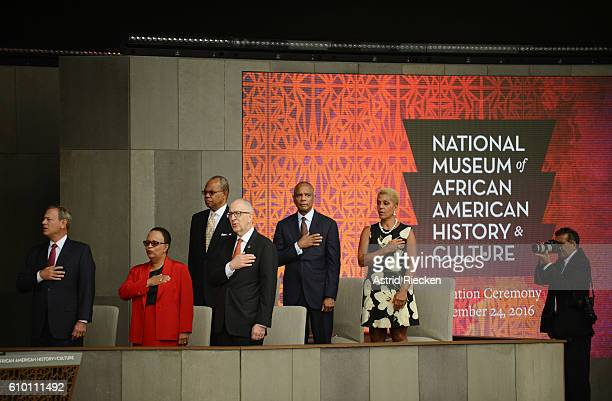 Dignitaries stand up during the presentation of the colors and the performance of the national anthem during the dedication of the National Museum of...