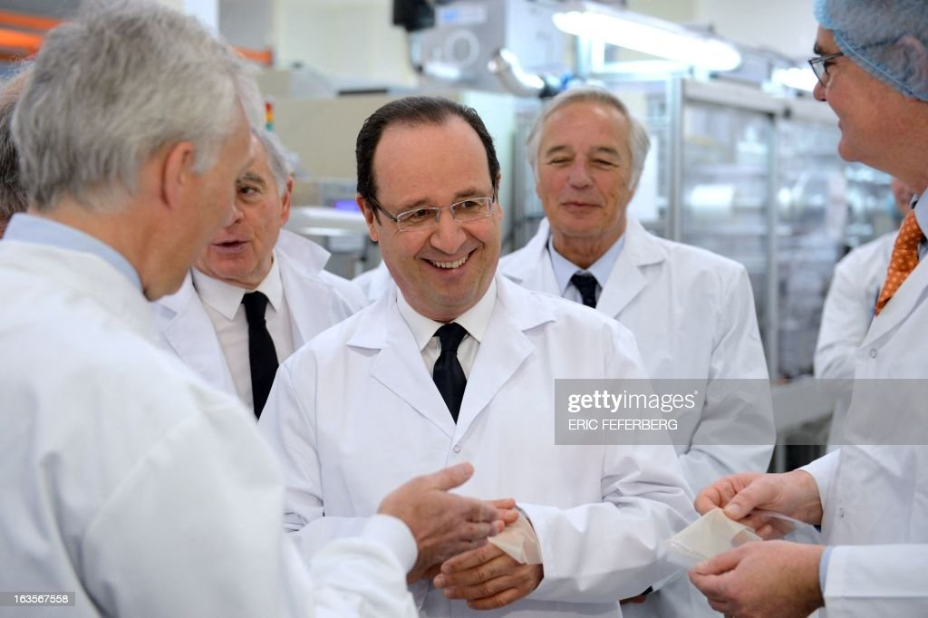 Dijon Mayor Francois Rebsamen (R) watches French President Francois Hollande (L) put a dressing on his hand as he visits the adhesive bandages Urgo industry plant on March 12, 2013 in Chevigny-Saint-Sauveur on the second of his two-day visit to Burgondy.