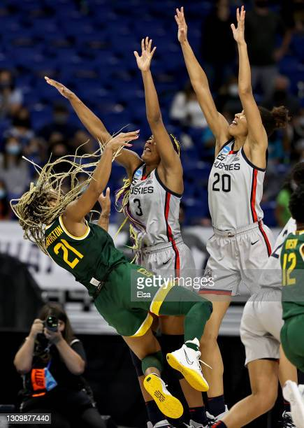DiJonai Carrington of the Baylor Lady Bears tries to take a shot as Aaliyah Edwards and Olivia Nelson-Ododa of the UConn Huskies defend in the final...