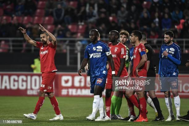 Dijon's and Amiens' players walk on the pitch as Amiens' French defender Prince Desir Gouano reported hearing racist insults during the French L1...