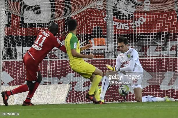 Dijon's Cap Verdian forward Julio Tavares shoots and scores against Nantes' French defender Koffi Djidji and Nantes' French goalkeeper Ciprian...