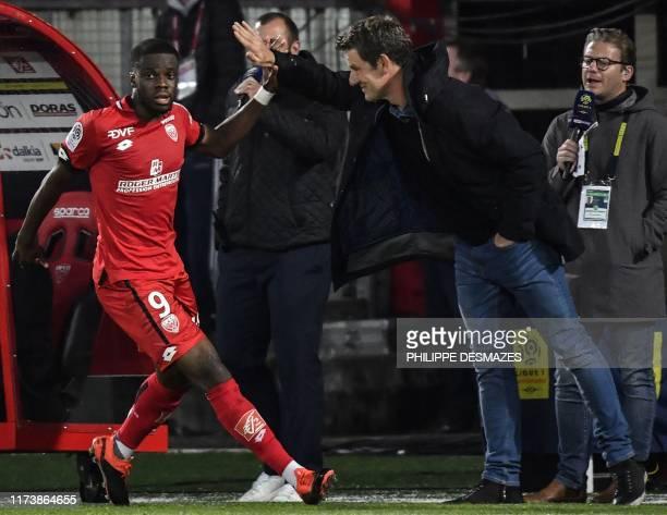 Dijon's English forward Stephy Mavididi is congratulated by Dijon's French coach Stephane Jobard during the French L1 football match between Dijon...