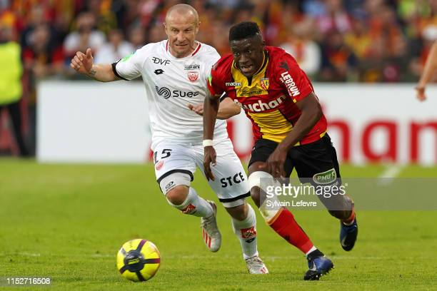 Dijon's Florent Balmont and Lens JeanRicner Bellegarde compete for the ball during the French L1L2 first leg playoff football match between Racing...