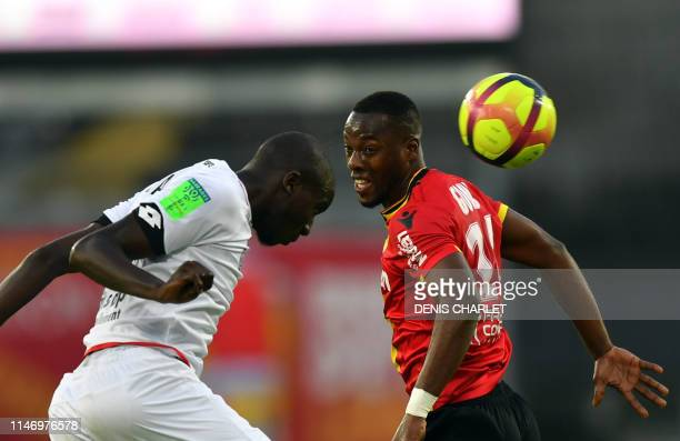 Dijon's French defender Cedric Yambere vies with Lens's forward Simon Banza during the French L1L2 first leg playoff football match between Lens and...