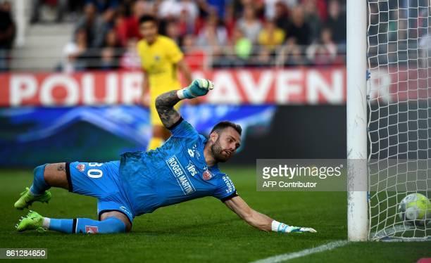 Dijon's French goalkeeper Baptiste Reynet dives as he takes a goal scored by Paris SaintGermain's Belgian defender Thomas Meunier during the French...