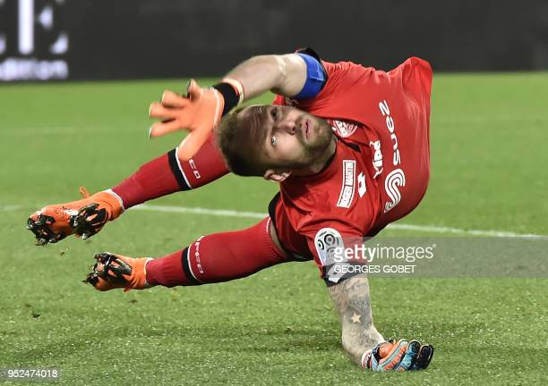 TOPSHOT Dijon's French goalkeeper Baptiste Reynet jumps to catch the ball during the French L1 football match between FC Girondins de Bordeaux and...