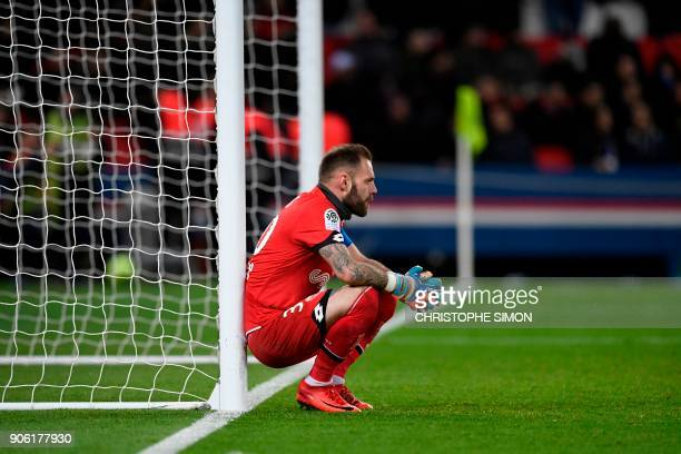 Dijon's French goalkeeper Baptiste Reynet leans on the goal post after missing to stop a goal during the French L1 football match between Paris...
