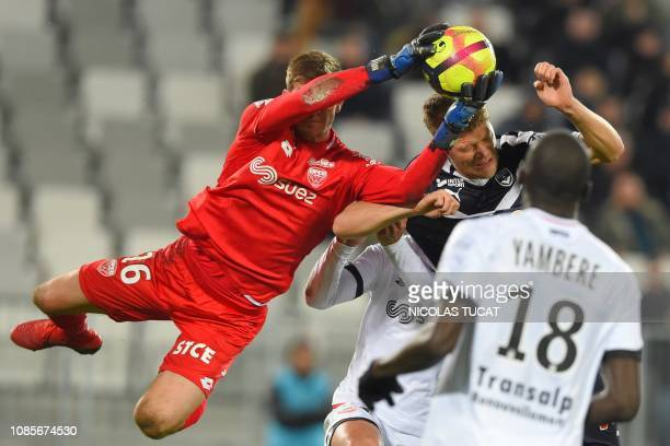 Dijon's French goalkeeper Bobby Allain makes a save in front of Bordeaux's Danish forward Andreas Cornelius during the French L1 football match...