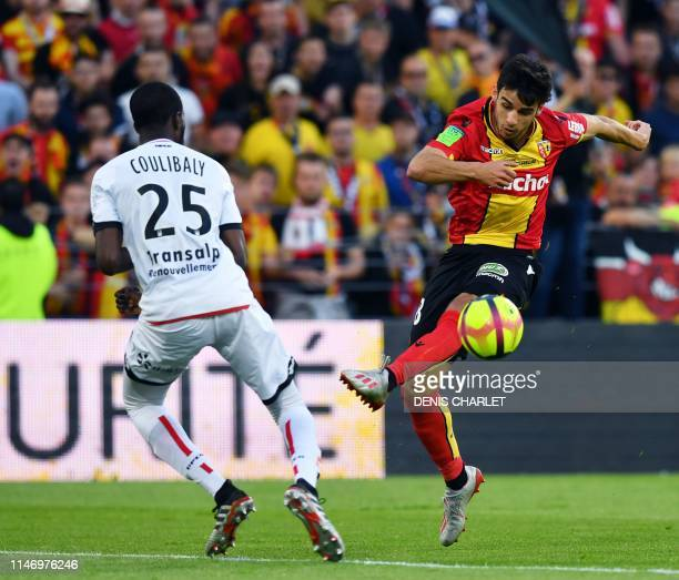 Dijon's French midfielder Senou Coulibaly vies with Lens' French midfielder Fabien Centonze during the French L1L2 first leg playoff football match...