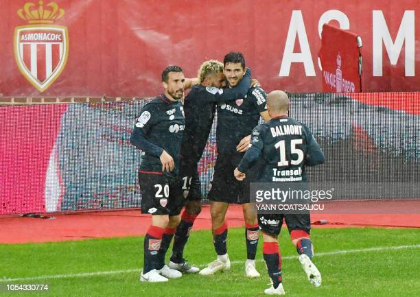 Dijon's French-Algerian midfielder Mehdi Abeid celebrates with teammates after scoring a goal during the French L1 football match AS Monaco FC vs...