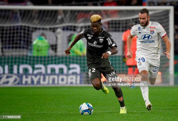 Dijon's Gabonaise midfielder Didier Ndong runs for the ball with Lyon's French midfielder Lucas Tousart during the French L1 football match between...