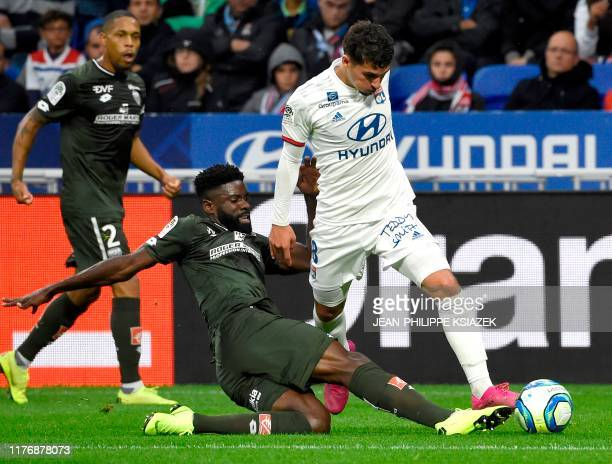 Dijon's Gabonese defender Bruno Ecuele Manga challenges Lyon's French midfielder Houssem Aouar during the French L1 football match between Lyon and...