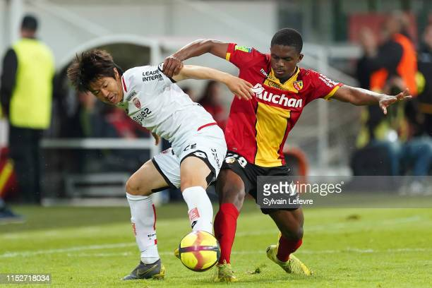 Dijon's Kwon Chang-hoon and Lens' Cheick Doucoure compete for the ball during the French L1-L2 first leg play-off football match between Racing Club...