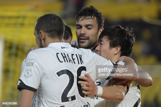 Dijon's South Korean midfielder Chang Hoon Kwon celebrates with teammates after scoring a goal during the French L1 football match between Nantes and...