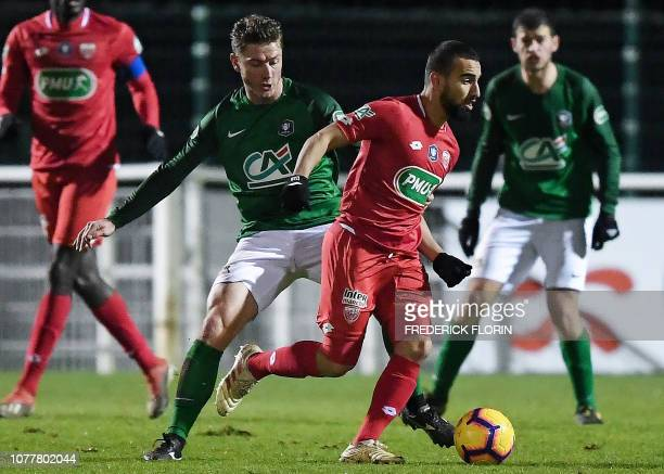 Dijon's Tunisian forward Naim Sliti fights for the ball with Schiltigheim's French defender Jordan Gasser during the French Cup football match...