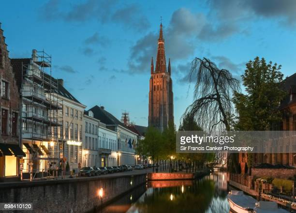 Dijver canal in Bruges illuminated at dusk with medieval Church of our Lady brick-built bell tower on background, Belgium