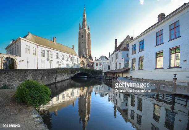 Dijver canal with medieval bridge and world's tallest brick-built tower of 'Church of our Lady' reflected in the waters of Bruges, Flanders, Belgium, a UNESCO heritage site