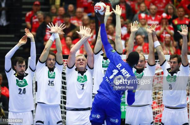 Dika Mem of France throws a shot over a wall of players of Germany during the 26th IHF Men's World Championship 3rd place match between Germany and...