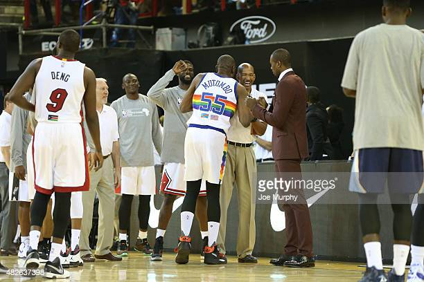 Dikembe Mutombo of Team Africa greets Assistant Coach Monty Williams against Team World during the NBA Africa Game 2015 as part of Basketball Without...