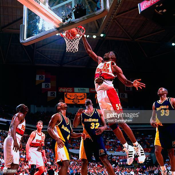 Dikembe Mutombo of the Atlanta Hawks dunks against Dale Davis of the Indiana Pacers during a game in 1997 at the Omni Center in Atlanta Georgia NOTE...