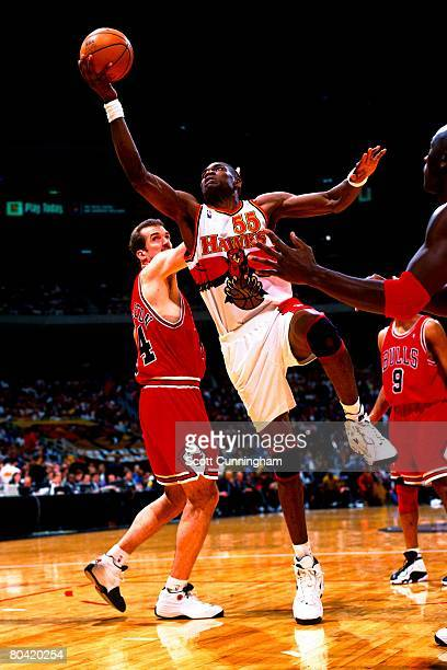 Dikembe Mutombo of the Atlanta Hawks shoots against Bill Wennington of the Chicago Bulls during the game at the Georgia Dome on March 27 1998 in...