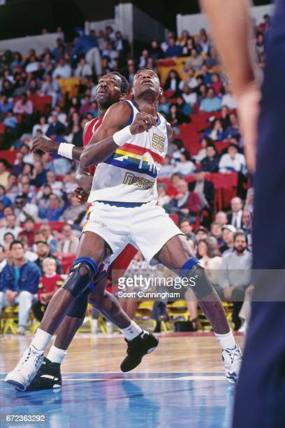 Dikembe Mutombo of the Denver Nuggets boxes out against the Houston Rockets during a game played circa 1990 at McNicholls Arena in Denver Colorado...