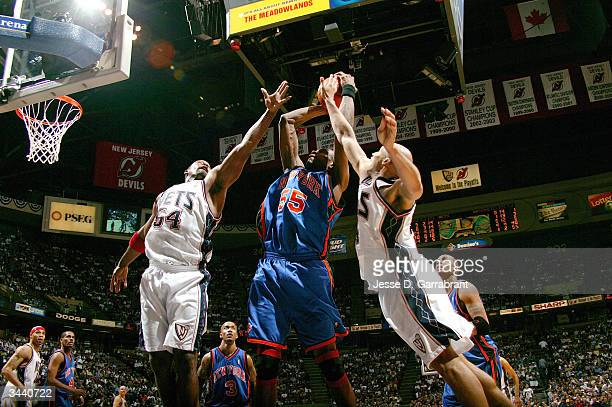 Dikembe Mutombo of the New York Knicks attempts to fight for the rebound against Richard Jefferson and Rodney Rogers of the New Jersey Nets during...
