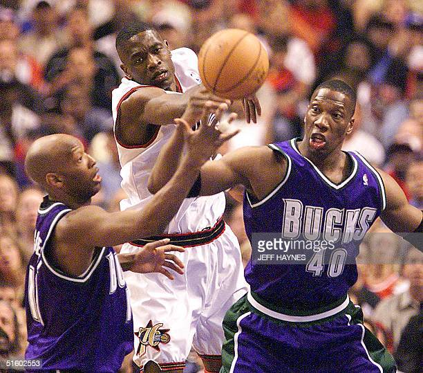 Dikembe Mutombo of the Philadelphia 76ers fights for the ball with Sam Cassell and Ervin Johnson of the Milwaukee Bucks in the NBA Eastern Conference...